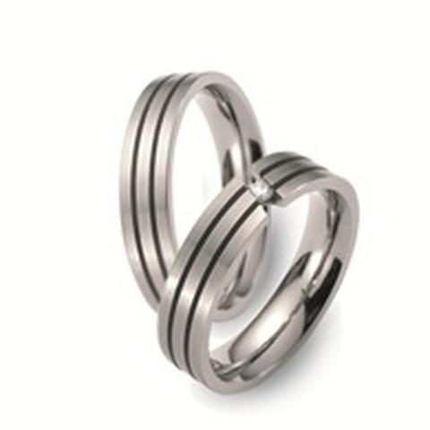 Titanium trouwringen, welke een breedte hebben van 5 mm. De ring is prachtig versierd met twee smalle, zwarte keramische ringen. Als middelpunt is in de dames trouwring een zwevende, briljant geslepen diamant van 0,05 ct gezet.