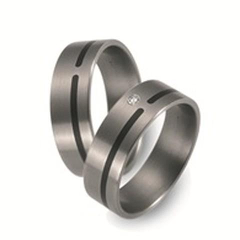 Tijdloze trouwringen van titanium van 7 mm breed. De ring heeft een strakke vormgeving. De smalle band van keramiek steekt mooi af bij het zilvergrijs van het titanium. In de dames trouwring is een briljant geslepen diamant van 0,03 ct gezet.