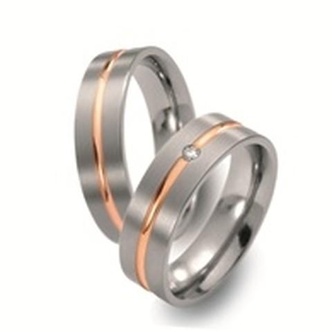 Strakke titanium trouwringen van 6 mm breed met 18 karaats geelgouden smalle binnenbaan. In de dames trouwring schittert een diamant geslepen briljant.