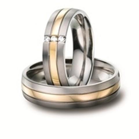 Deze opvallende trouwringen bestaan uit titanium en 18 karaat geelgoud. Beide ringen zijn onderverdeeld in 3 banen, de buitenste banen zijn uitgevoerd in titanium en de binneste baan bestaat uit geelgoud! Dan ziet u in het midden van de ring voor haar ook nog 3 schitterende diamanten in een populaire zetting, genaamd de brugzetting!