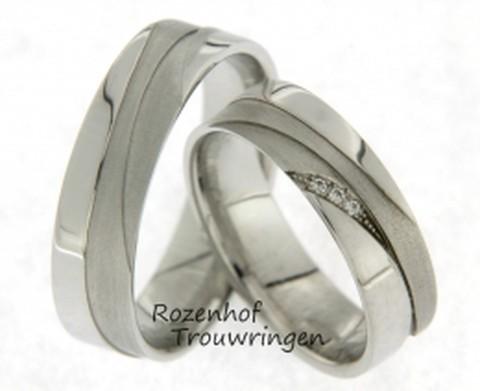 Glanzende, 6 mm brede, witgouden trouwringen met opvallende vlakverdeling dat zorgt voor een moderne uitsraling. De ring is verdeeld in verschillende vlakken glanzend witgoud en matt witgoud. In de dames trouwring zijn drie fonkelende diamanten gezet.