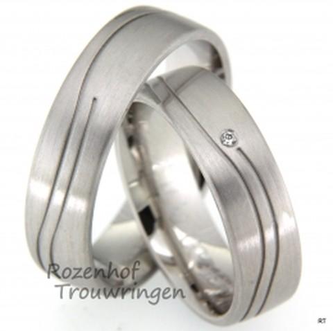 Matte trouwringen uitgevoerd in witgoud. In beide ringen ziet u een subtiel gegolfd lijnenspel. En voor de bruid hebben we aan het einde van het lijnenspel nog een stralende diamant geplaatst.