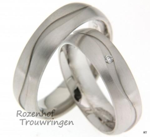 Witgouden trouwringen met matte finish. Een golvende, dieperliggende lijn is rondom in de ring verwerkt. Een briljant geslepen diamant dobbert als het ware in de golvende lijn mee.