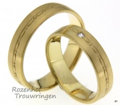 Er is uitgegaan van een strakke vormgeving bij deze 5 mm brede, matte geelgouden trouwringen. De speelse vormgeving in het midden van de ring heft het strakke karakter van de ring echter op. In de dames trouwring prijkt een briljant geslepen diamant van 0,025 ct.