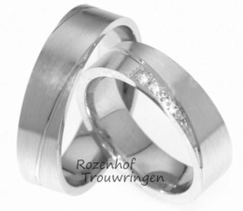 Chique witgouden trouwringen, welke een breedte hebben van 6 mm. Een fijne diagonale lijn doorbreekt de strakheid van de ring. De ringen zijn mat afgewerkt. In de dames trouwring zijn in de punt van de lijn, 5 briljant geslepen diamanten van tezamen 0,15 ct gezet.