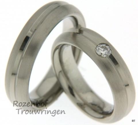 Mooie trouwringen uitgevoerd in witgoud met een matte finish. Gedurende beide ringen loopt een glanzende lijn dat de matte textuur breekt. In de ring voor haar bevindt zich een reusachtige diamant.