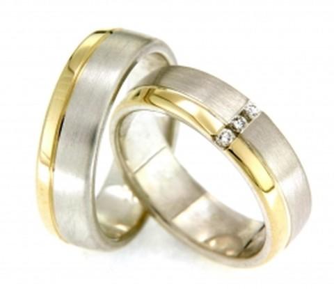 Stijlvolle trouwringen van wit- en geelgoud. De ring bestaat uit een brede band van mat witgoud en een smallere band van geelgoud in hoogglans. In de dames trouwring is een pad, verlicht met drie fonkelende briljant geslepen diamanten van in totaal 0,075 ct, gezet.