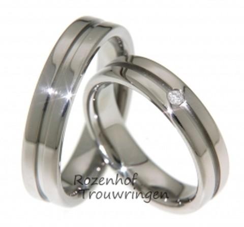 Hoogglanzende titanium trouwringen van 5 mm. breed. Een dieper liggende groef verdeeld de ring in twee banen. In de dames trouwring fonkelt een briljant geslepen diamant van 0,03 ct.