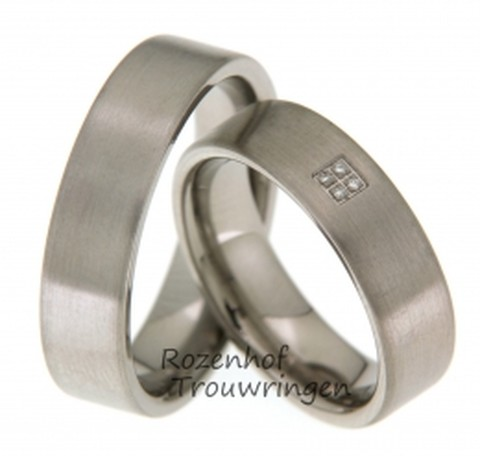 Moderne trouwringen van titanium, welke een breedte hebben van 6 mm. De ringen zijn mat afgewerkt. De dames ring krijgt extra cachet door de plaatsing van 4 briljant geslepen diamanten van 0,02 ct.