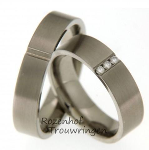 Modern vormgegeven titanium trouwringen van 5,5 mm. breed. De ringen hebben een matte finish. In de heren ring is overdwars een verdiepte groef gezet. In deze groef zijn in de dames trouwring 3 briljant geslepen diamanten van 0,06 ct. geplaatst.