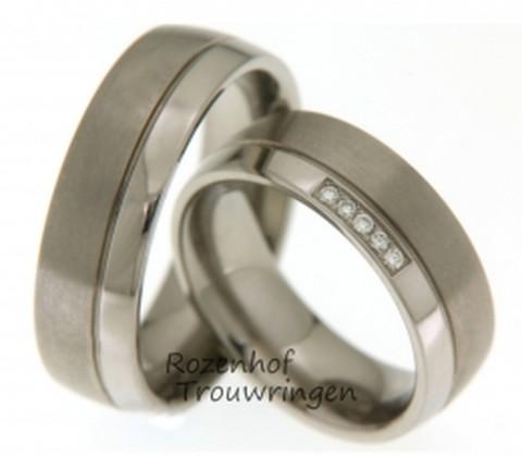 Titanium trouwringen, door een groef in twee banen verdeelt, een glanzende baan en een matte baan. De ringen zijn 7 mm. breed. In de dames trouwring zijn, in de glanzende baan, 5 briljant geslepen diamanten van 0,05 ct. gezet.