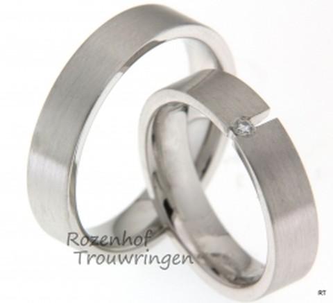 Moderne witgouden trouwringen met matte finish, die opvallen door hun strakke vormgeving. De ringen zijn 5 mm breed. De dames trouwring is bezet met een briljant geslepen diamant van 0,03 ct, die opvalt door zijn unieke plaatsing.