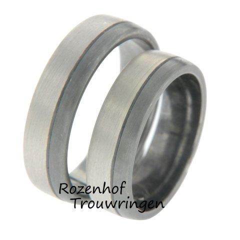 Trouwringen van 6 mm breed, bestaande uit 9 krt witgoud en palladium. De dames trouwring is bezet met 3 briljant geslepen diamanten van tezamen 0,75 ct. 2 harten, 2 ringen en 1 liefde.