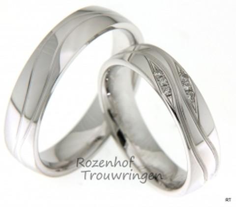 Glanzende witgouden trouwringen van 5 mm breed met golvende lijnen. In de dames trouwring zijn, op unieke wijze, 6 briljant geslepen diamanten gezet in een mooie golvende beweging.