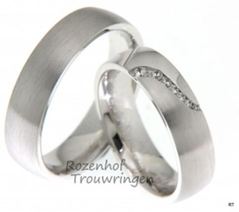 Matte, witgouden trouwringen van 6,5 mm breed van ons design. In de dames trouwring is op geraffineerde wijze een lijn van vele briljant geslepen diamanten gezet van in totaal 0,096 ct.