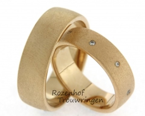 Robuuste, warmgouden trouwringen met matte finish. In de dames trouwring zijn briljant geslepen diamanten gezet als tegenpool van deze stoere ring.