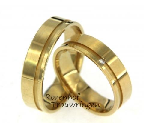 Glanzende geelgouden trouwringen. Door beide ringen loopt een uitgediepte lijn en daarin is, bij de damesring, ook een briljant geslepen diamant geplaatst.