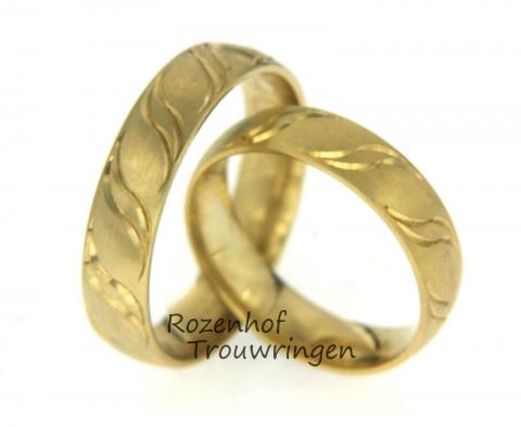Tijdloze, geelgouden trouwringen. De ringen hebben beide een twistend motief, rondom de hele ring ziet u twistende vromen. Dat staat symbool voor allemaal persoonlijke verbindingen.