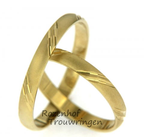 Neutrale, geelgouden trouwringen. De ringen zijn smal en hebben rondom de gehele ring diagonale strepen. Het design is glanzend, dit staat prachtig bij de matte ring.