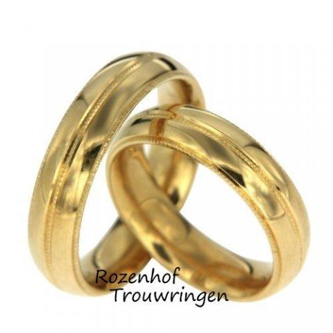 Geheel glanzende trouwringen bestaand uit geelgoud. De ring heeft drie hele smalle lijnen die een stippelend motief hebben. In combinatie met de rest van de ring staat dit erg mooi en is het een prachtig plaatje samen!