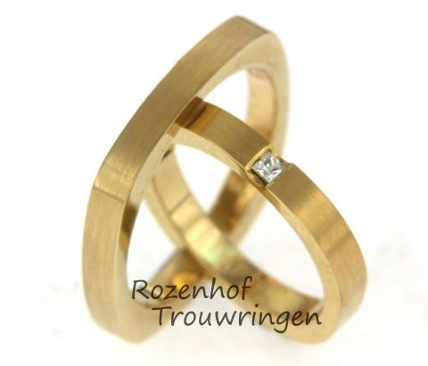Neutrale geelgouden trouwringen. De ringen hebben een strakke vorm en zijn afgewerkt in mat geelgoud. De diamant is princess geslepen. Van buiten lijken de ringen vierkant en van binnen rond.