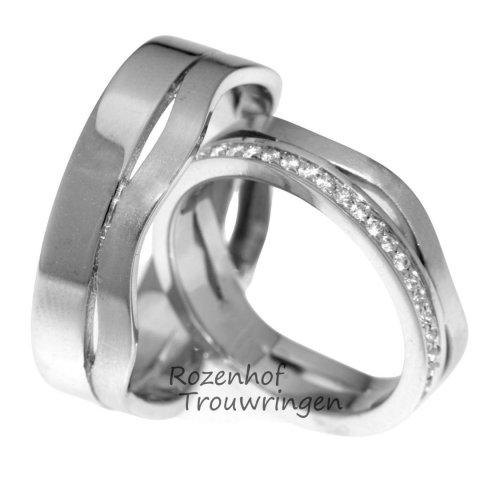 Dynamische trouwringen van witgoud met diamanten. de 6 mm brede trouwringen hebben een statische kant en een beweeglijke kant. In de dames trouwring is een fonkelende rij van 23 briljant geslepen diamanten van in totaal 0,23 ct gezet.