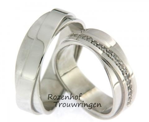 Gecompliceerde, witgouden trouwringen met fonkelende diamanten. De witgouden ringen zijn kruislings over elkaar gezet. In de dames trouwring volgen 19 briljant geslepen diamanten het bovenpad.