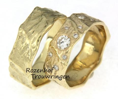 Deze ringen zijn uitgevoerd in geelgoud en hebben een aparte touch, dit setje is namelijk ambachtelijk en maakt zichzelf zeer exclusief door middel van de diamanten die geen vaste grote hebben, zo ziet u in het midden van de ring een reusachtige diamant met daaromheen allemaal kleinere diamantjes.