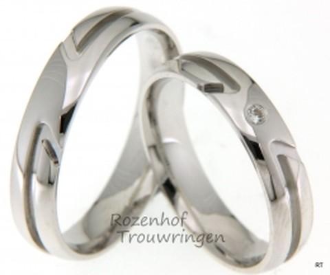 Glanzende, witgouden trouwringen van 4,5 mm breed. De bijzondere belijning geeft deze trouwringen een speciaal karakter. In de dames trouwring is een briljant geslepen diamant gezet van 0,03 ct.