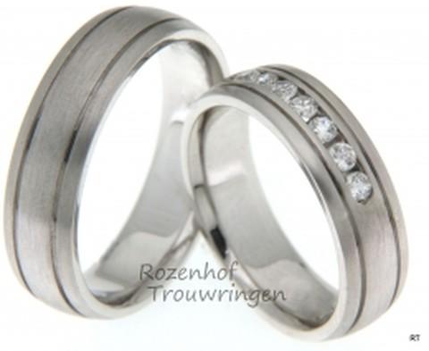 Witgouden trouwringen van 6 mm breed met matte finish. In de ring zitten twee smalle groeven. In de dames trouwring zijn 7 briljant geslepen diamanten gezet van in totaal 0,32 ct.