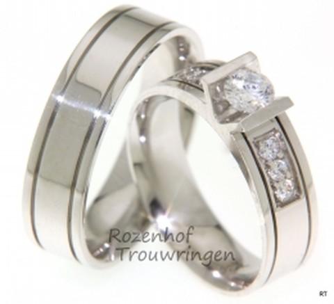 Luxueuse trouwringen van glanzend witgoud met twee subtiele dieperliggende lijnen. In de V-zetting van de dames trouwring, is een schitterende briljant geslepen diamant gezet van 0,35 ct. Tevens zijn er 6 briljant geslepen diamanten van 0,03 ct. aan beide zijden van deze zetting geplaatst.De ringen zijn 6 mm breed.