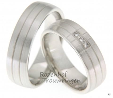 Opvallend door hun indeling van de belijning, zijn deze witgouden trouwringen met matte finish. De ringen zijn 6,5 mm breed. In de dames trouwring zijn drie briljant geslepen diamanten van in totaal 0,036 ct gezet.