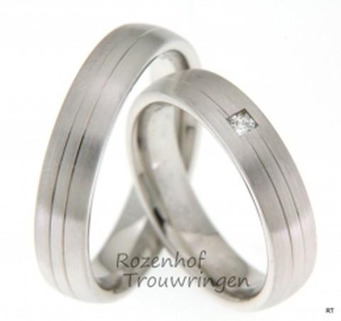 Gematteerde witgouden trouwringen met een breedte van 5 mm. In de dames trouwring prijkt een mooie prinses geslepen diamant van 0,06 ct.