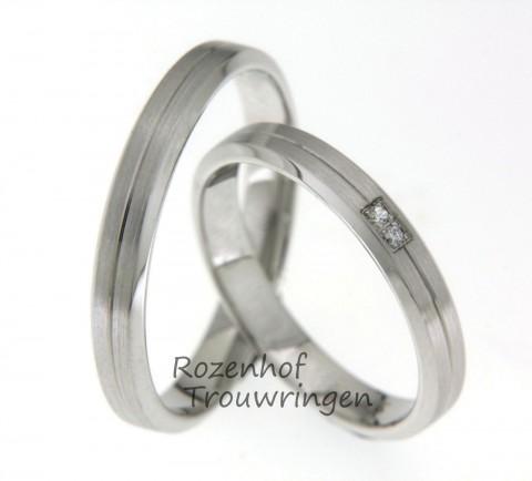 Koele, witgouden trouwringen met fijne lijn die de ring in twee delen verdeeld. In de dames trouwring zijn 2 fonkelende, briljant geslepen diamanten, verzonken in de ring gezet.