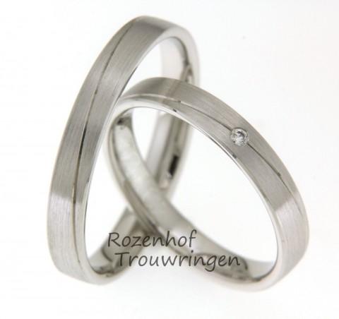 Moderne, witgouden trouwringen met fijne, glanzende lijn. De ring heeft een matte afwerking. In de dames trouwring is een briljant geslepen diamant gezet.