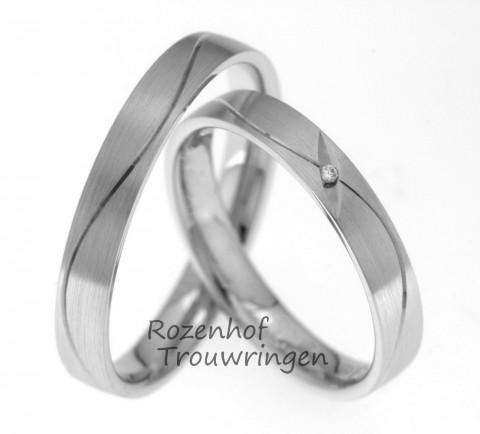 Witgouden trouwringen met matte afwerking. Een dartel, hoogglanzend lijntje loopt over de ring. De glinsterende diamant laat haar licht stralen over het dartelende lijntje in de dames trouwring.