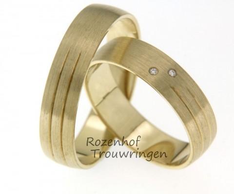 Subtiel versierde trouwringen van geelgoud. De twee subtiele lijnen zijn aan één kant van de ring aangebracht. In de dames trouwring zijn 2 schitterende, briljant geslepen diamanten gezet.