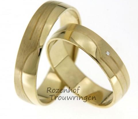 Geelgouden trouwringen met aparte details. De ring is zowel in een bijzonder mat gedeelte als een bijzonder hoogglanzende vorm afgewerkt. In de dames trouwring is een fonkelende diamant gezet.
