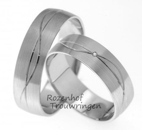 Klassiek gevormde trouwringen van witgoud versierd met een romantisch golvende en een kaarsrechte lijn. Twee uitersten samen in een harmonieuze ring. In de dames trouwring is een briljant geslepen diamant gezet.