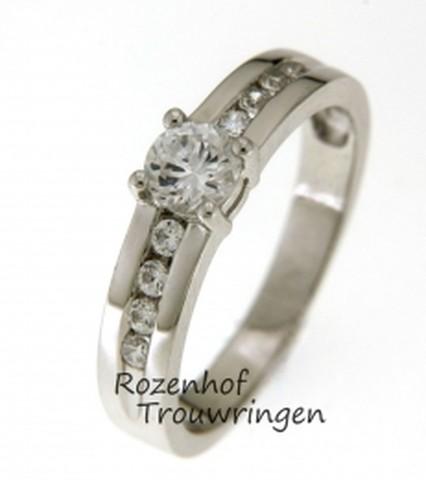 Magische verlovingsring, rijkelijk versierd met diamanten. De verlovingsring is gemaakt van witgoud en bezet met 8 kleinere briljant geslepen diamanten en als middelpunt 1 grote briljant geslepen diamant.