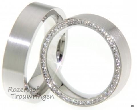 Een briljant paar, deze matte witgouden trouwringen van 6 mm breed. In de dames trouwring prijken aan de buitenkant van de ring 92 briljant geslepen diamanten.