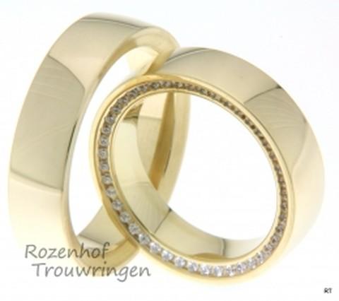 Prachtige, glanzende geelgouden trouwringen. De ringen zijn 6 mm breed. In de dames trouwring is aan de zijkant van de ring, een schitterende rand van briljant geslepen diamanten geplaatst.