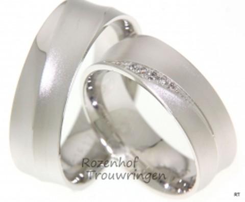 Matte witgouden trouwringen met lichte golving. De ringen zijn 7 mm breed. In de dames trouwring zijn, in een mooie vorm, 7 briljant geslepen diamanten gezetin verschillende groottes.