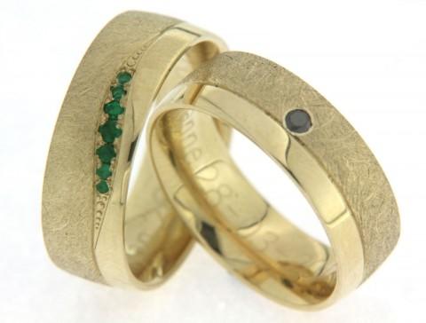 Bijzondere, geelgouden trouwringen met smaragd en zwarte diamant. Deze ambachtelijke ringen zijn bijzonder door de edelstenen die erin verwerkt zijn. In de dames trouwring zijn 7 smaragden gezet. In de heren trouwring is een mysterieuze, zwarte diamant gezet. Het contrast van de krasmatte finish en de hoogglans finish, maakt dit paar nog specialer.
