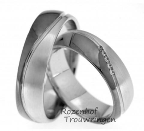 Elegante trouwringen van witgoud met ruthenium gedeelte. De golvende beweging zorgt voor een ring van sierlijke eenvoud. De ringen zijn 6 mm. breed. In de dames trouwring zijn, in een schuine rij, 5 briljant geslepen diamanten van 0,038 ct. gezet.