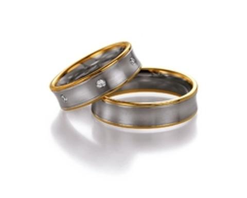 Fraaie, bicolor trouwringen van wit- en geelgoud van 6 mm breedte met 6 briljant geslepen diamanten van in totaal 0,18 ct.