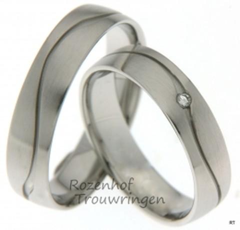 Witgouden, 4,5 mm brede, trouwringen met matte finish. In de ringen is een verdiepte golvende lijn gezet. In de dames trouwring is een briljant geslepen diamant geplaatst van 0,02 ct.