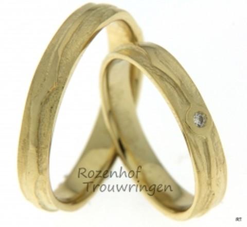 Ranke trouwringen van geelgoud met er bovenop gelegen grillige lijn. De ringen zijn 4,2 mm breed. In de dames trouwring is een briljant geslepen diamant verwerkt van 0,025 ct.