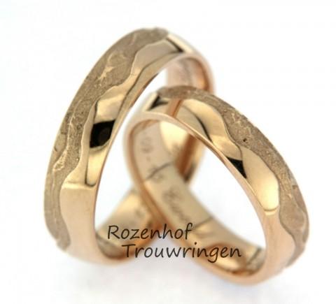 Spannende, ambachtelijke trouwringen van geelgoud. De helft van de ring bestaat uit een gegolfde grove structuur de andere helft is glad en hoogglanzend. Een spannend paar!