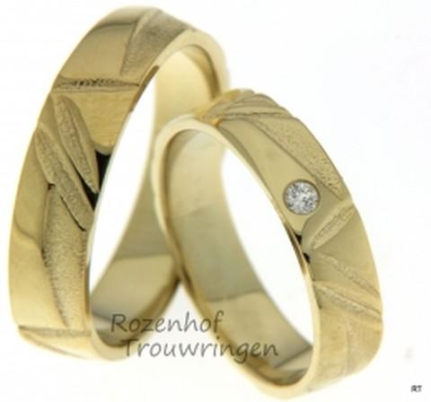 Deze 5,3 mm brede, ambachtelijke trouwringen van geelgoud hebben een mooie tekening. De matte, ruwe structuur afgewisseld met het gladde, glanzende oppervlakte geeft deze ringen een zeer apart uiterlijk. Voor extra glans in de dames trouwring zorgt een schitterende briljant geslepen diamant van 0,055 ct.